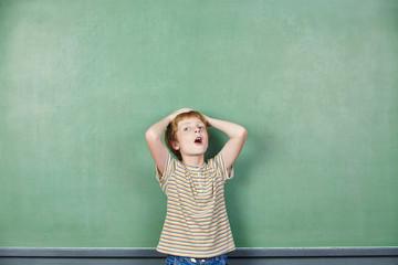 Kind schlägt Hände über dem Kopf zusammen