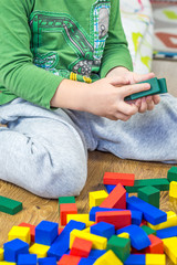 child is playing with multicolored cubes on wooden floor