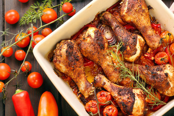 Roasted chicken drumsticks with vegetables in a pan on a wooden