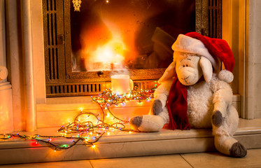 toy sheep sitting next fireplace at new year