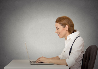 Side profile happy woman using working her laptop computer