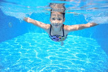 Happy active underwater child swims in pool, girl swimming