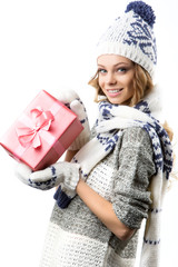 Portrait happy girl in sweater hat and mittens with boxes gifts