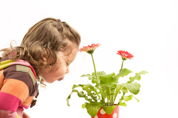 Little girl blowing over the flowers with eyes closed