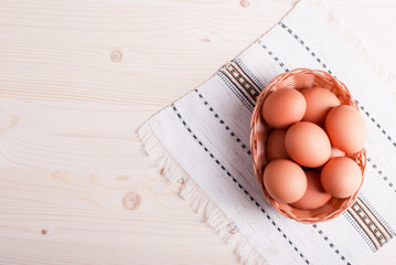 brown eggs in a wicker basket on a light wooden table top view
