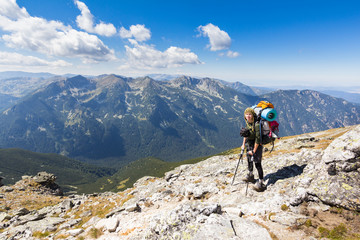 Fototapete - Woman backpacker standing mountain edge.