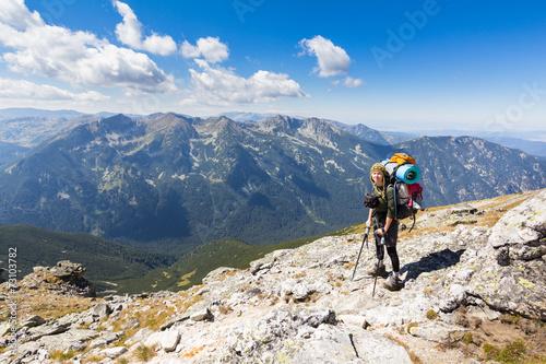 Wall mural Woman backpacker standing mountain edge.