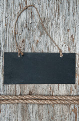 Chalkboard with rope on the old wood