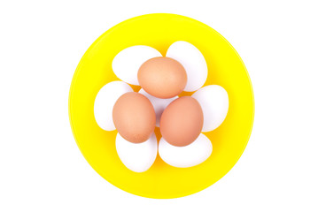several white eggs on top of brown eggs in a yellow beautifully