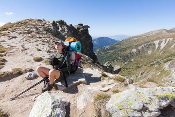 Fototapete - Woman backpacker sitting resting mountain peak.