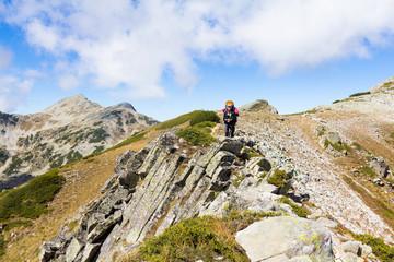 Fototapete - Woman backpacker standing mountain peak ridge.