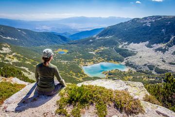Wall Mural - Woman sitting mountain edge above lake.
