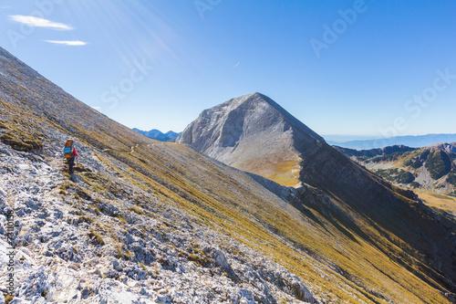 Fototapete Woman backpacker walking mountain slope trail.