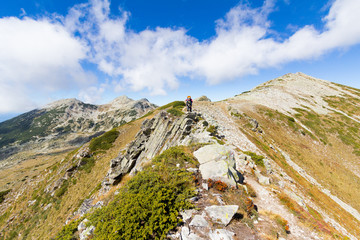 Fototapete - Backpacker standing mountain ridge.