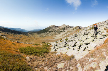 Fototapete - Backpacker woman walking rocky mountain slope.
