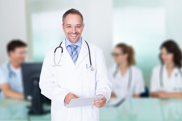 Doctor Holding Digital Tablet Against Team In Meeting Room