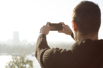 Man Taking Photo Of City And River With Mobile Phone Outdoor