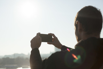 Man Taking Photo With Mobile Phone Of City On Sunny Day