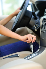 woman driver shifting the gear stick driving a car