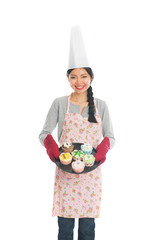 Young Asian girl baking bread and cupcakes, wearing apron and gl