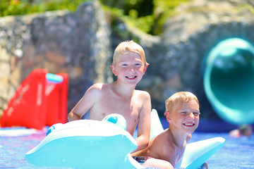 Two happy boys  having fun in swimming pool at summer