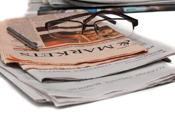 Glasses on the newspaper. Articles about markets.