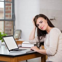 sympathische junge frau arbeitet zuhause am laptop