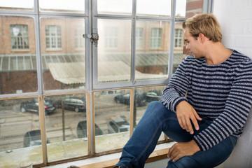 junger typ sitzt am fenster und schaut auf die straße