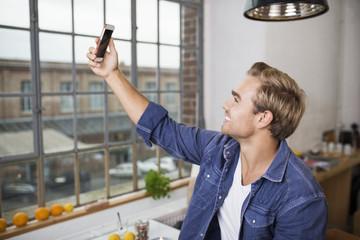 lachender mann macht ein selfie