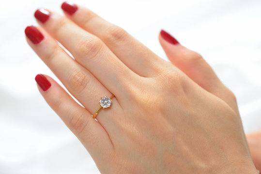 Wedding ring on hand of bride on white cloth