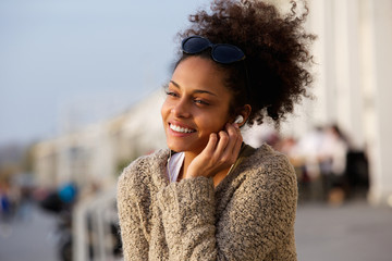 Happy young woman listening to music on earphones outdoors