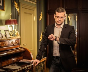 Middle-aged man looking at his wrist watch in luxury interior