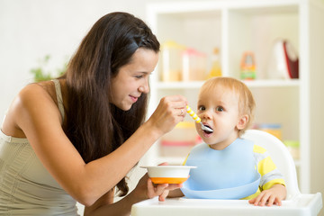 Mother spoon-feeding her child