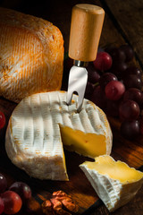 various types of cheese with grapes and nuts