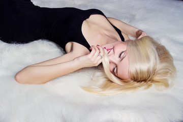 beautiful women a smile lying on white carpet in a black dress