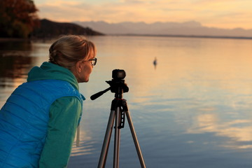 Cute woman movie sunset with swans on lake
