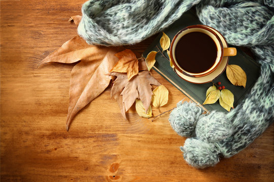 Top view of Cup of black coffee with autumn leaves, a warm scarf