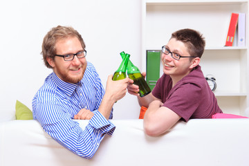 Two young guys with beer on the sofa