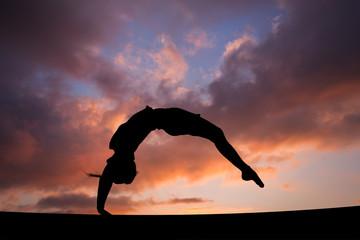 Fototapete - back handspring of female gymnast in sunset sky