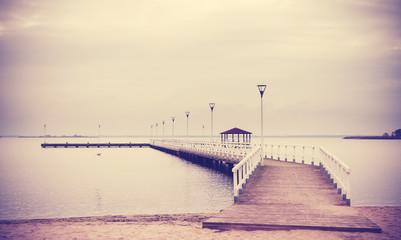 Vintage retro filtered wooden pier at sunset.