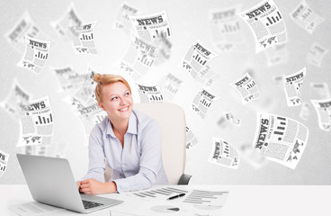 Business woman at desk with stock market newspapers