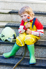 Funny little child of four years having fun as fireman, in unifo