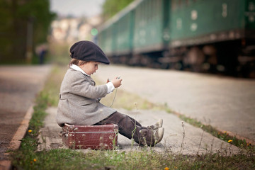 Boy, dressed in vintage coat and hat, with suitcase