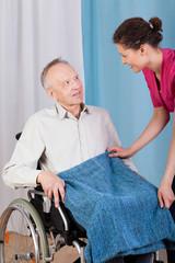 Nurse helping disabled man