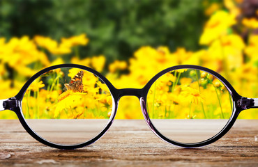 Wall Murals Yellow Vision concept. Eye glasses on wooden table outdoors
