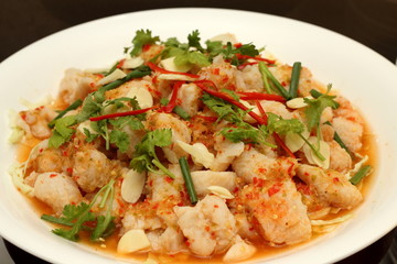 Spicy salad with  shrimp, fish and vegetables on white dish.