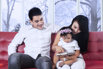 Asian family using tablet on couch
