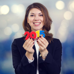Happy business woman holding a figure of 2015.