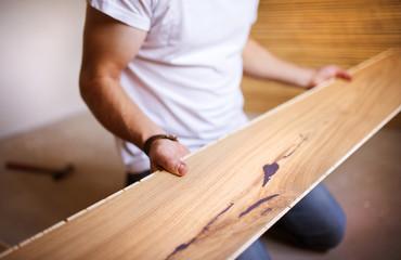 Obraz Handyman installing wooden floor - fototapety do salonu