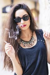 Glamorous brunette woman with sunglasses smoking.
